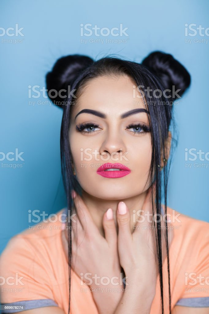 portrait of beautiful sexy brunette woman with hair of mouse on blue background stock photo