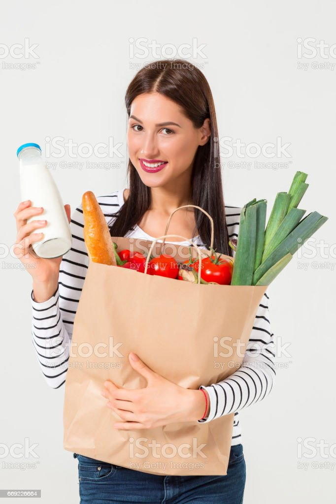 Portrait of beautiful smiling woman holding shopping paper bag with organic fresh food isolated on white background stock photo