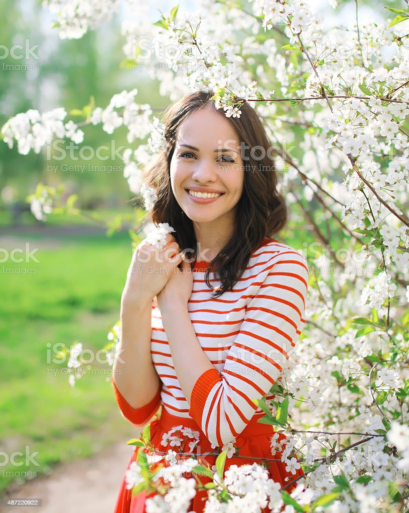 Portrait of beautiful smiling young woman in flowering spring ga stock photo