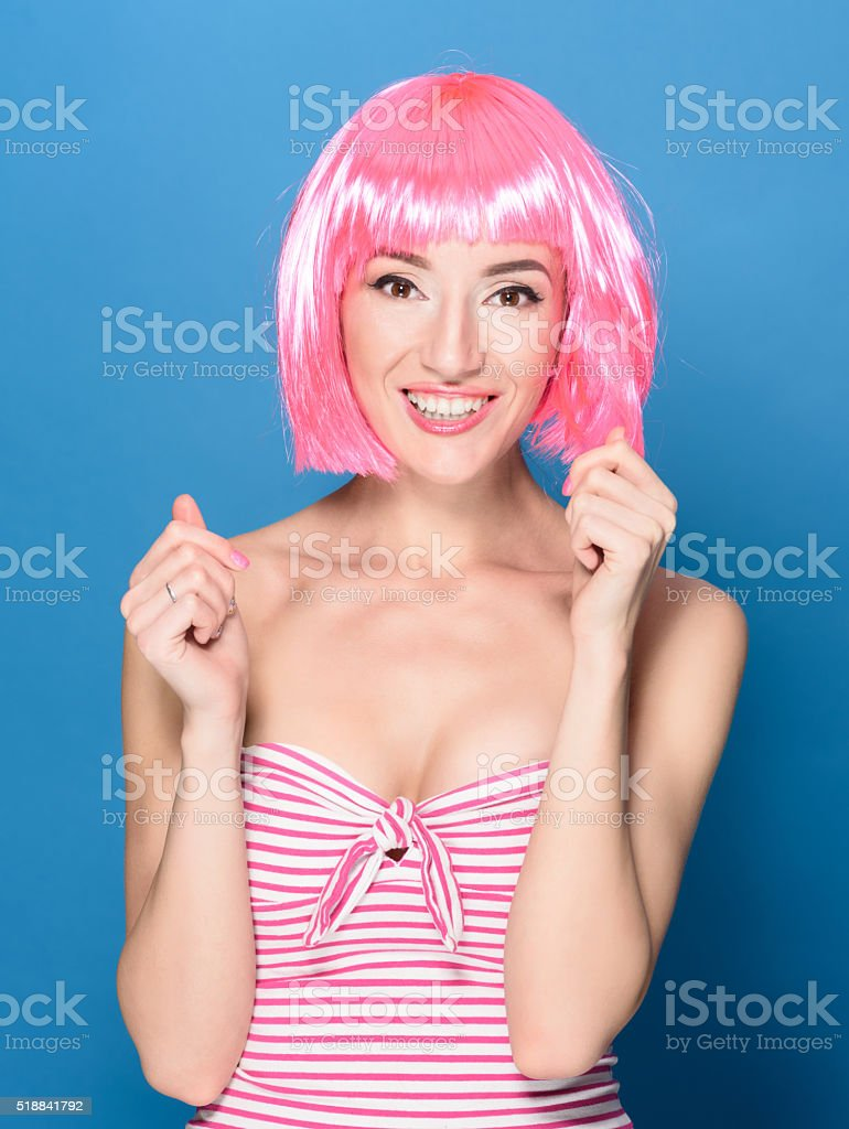 Portrait of beautiful smiling young woman with pink hair on stock photo