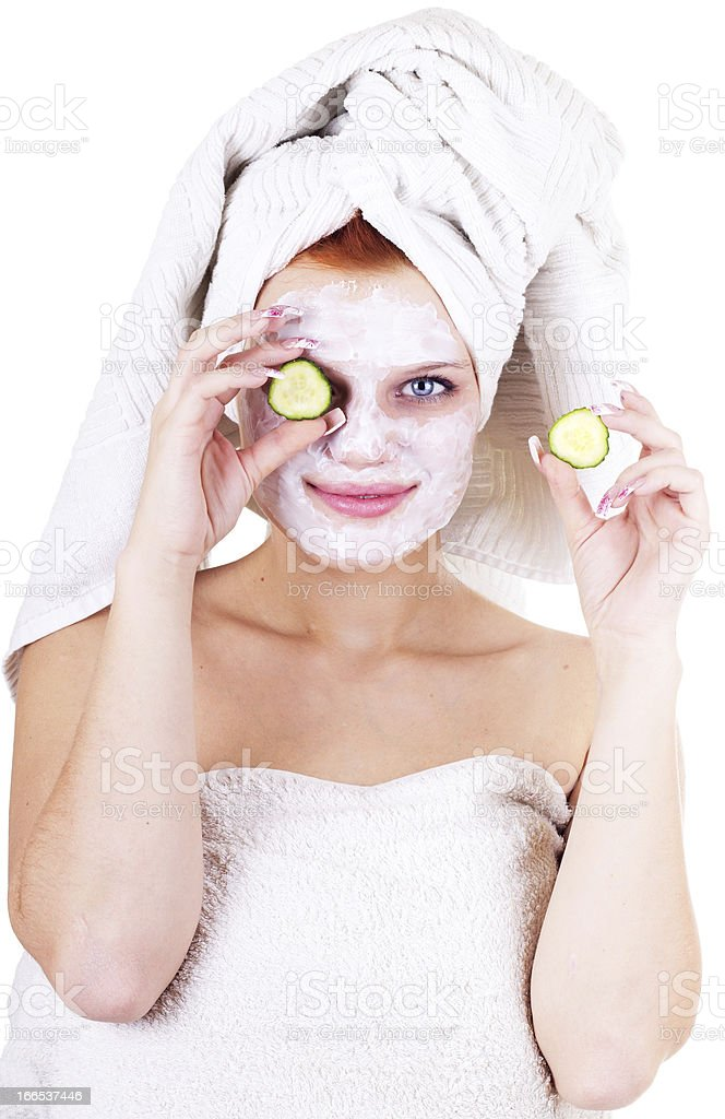 Portrait of beautiful woman applying facial mask and cucumbers royalty-free stock photo