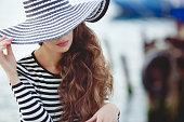 Portrait of beautiful woman in hat on the pier