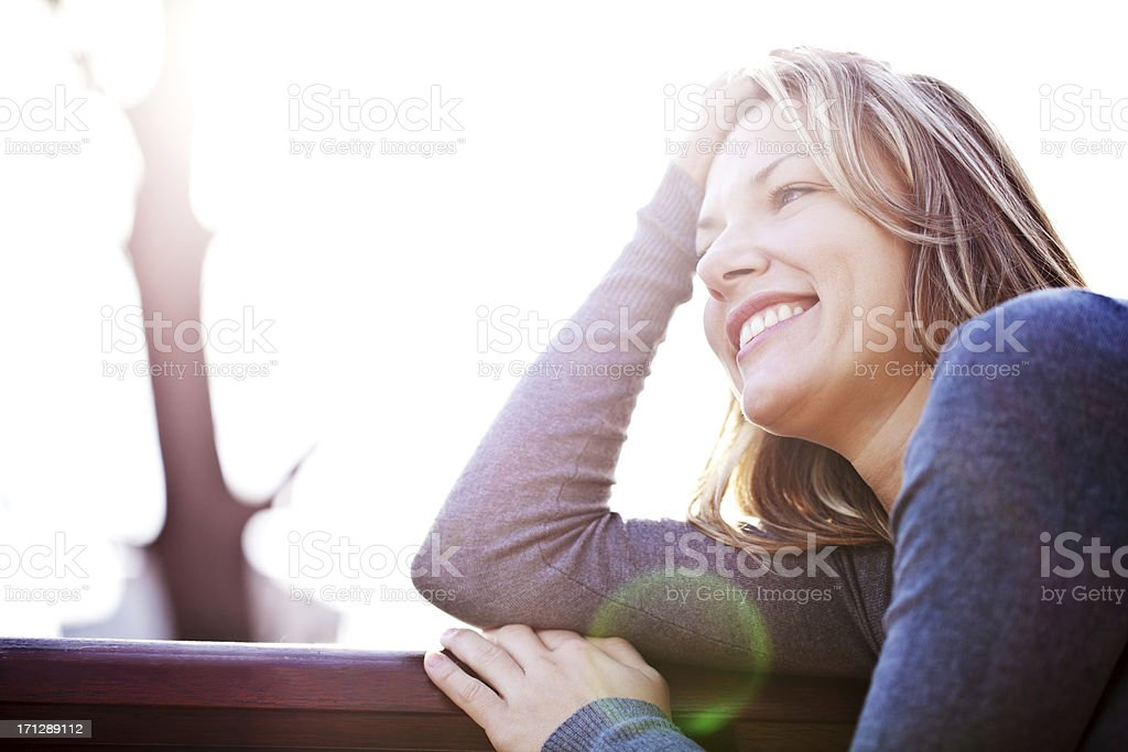 Portrait of beautiful woman leaned on the bench. stock photo