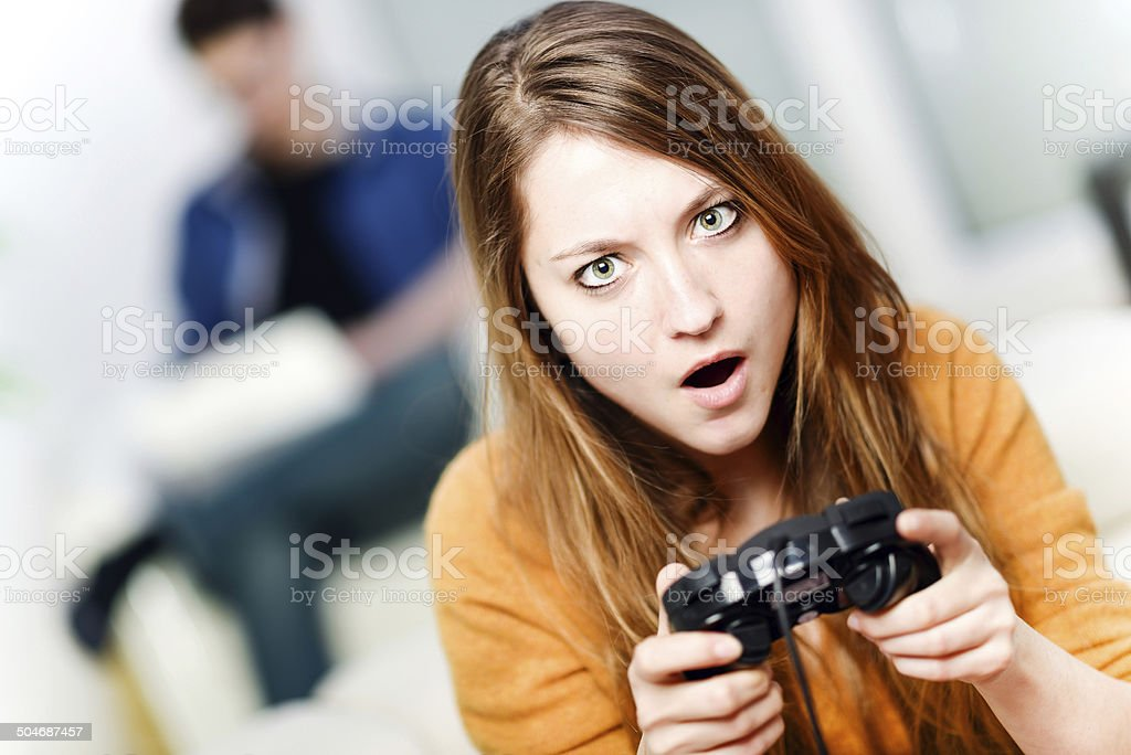 Portrait of beautiful woman playing videogame at home stock photo