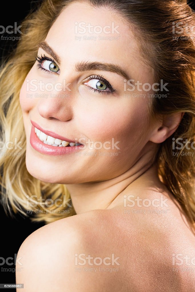 Portrait of beautiful woman smiling against black background stock photo