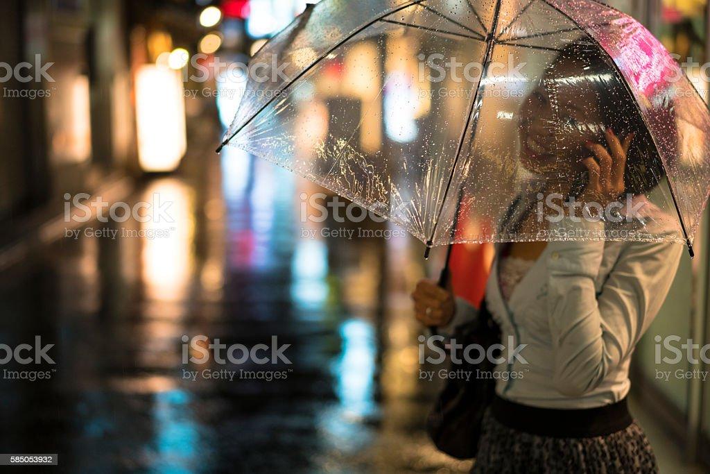 Portrait of beautiful woman talking under umbrella on mobile, Japan. stock photo