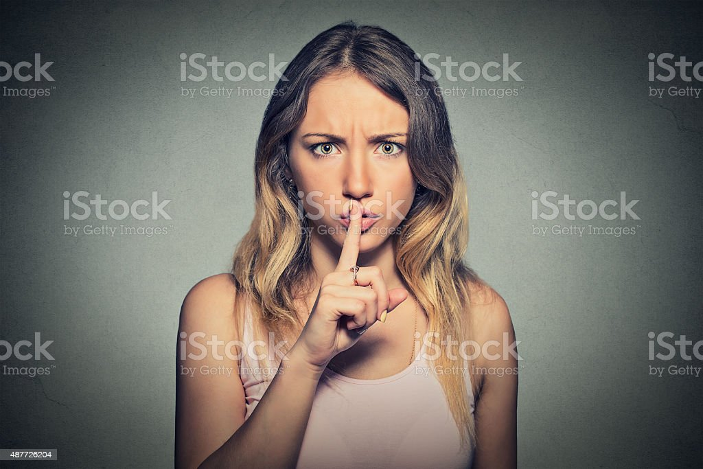 Portrait of beautiful woman with finger on lips gesture stock photo