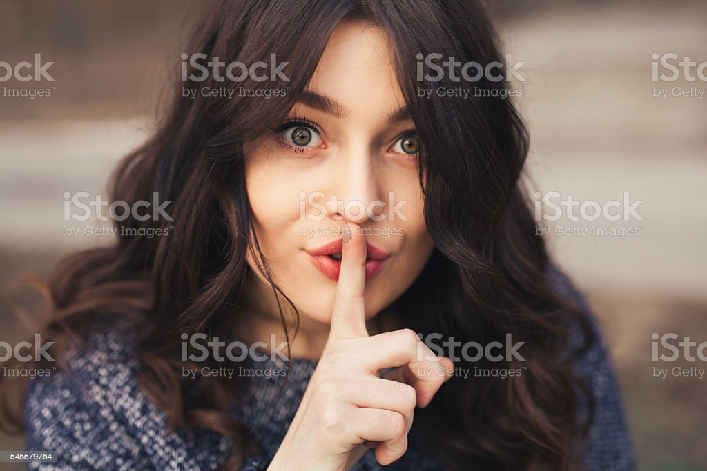Portrait of beautiful woman with finger on lips. stock photo