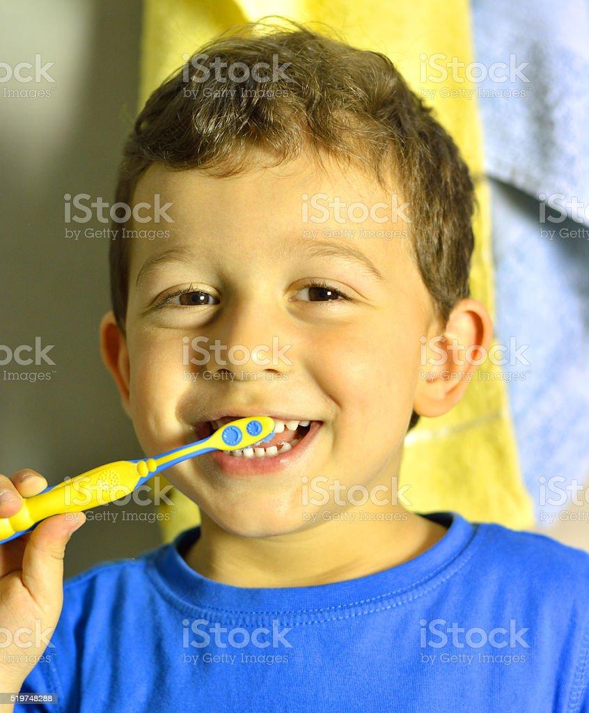 Portrait of Beautiful Young Boy Brushing his Teeth stock photo