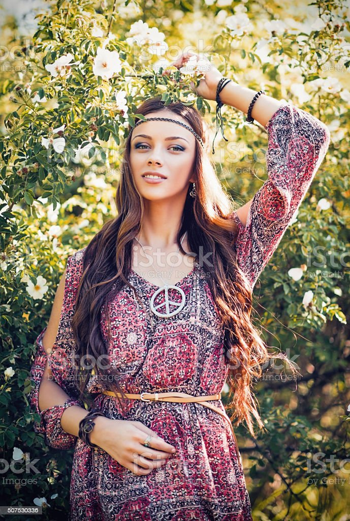 Portrait of beautiful young hippie girl among the flowers stock photo
