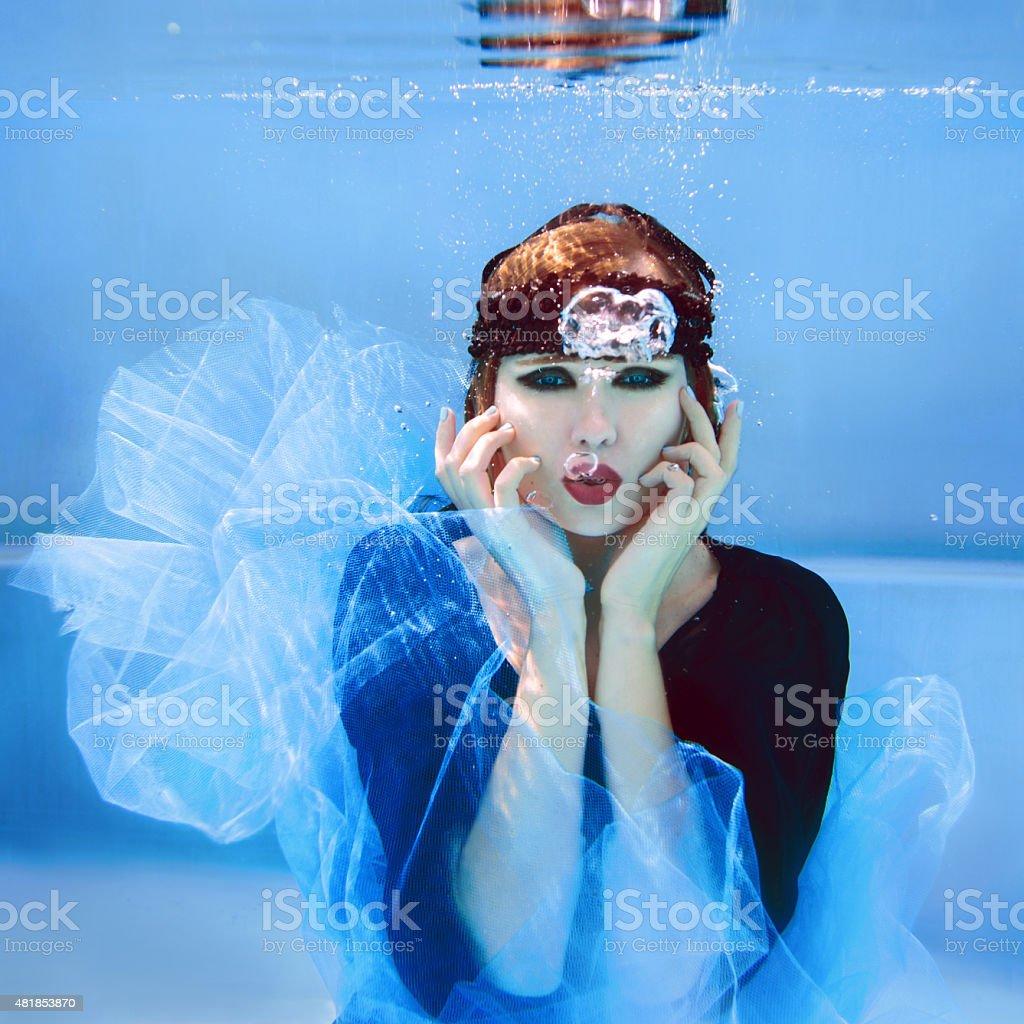 portrait of beautiful young stylish woman underwater stock photo
