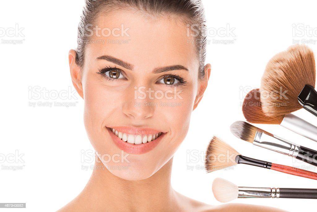 Portrait of beautiful young woman holding makeup brushes near face stock photo