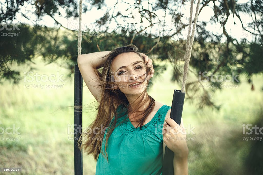 portrait of beautiful young woman in casual green dress stock photo