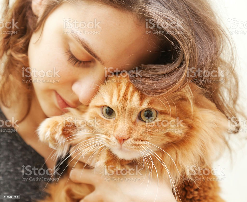 beautiful young woman 20 years with a fluffy red cat