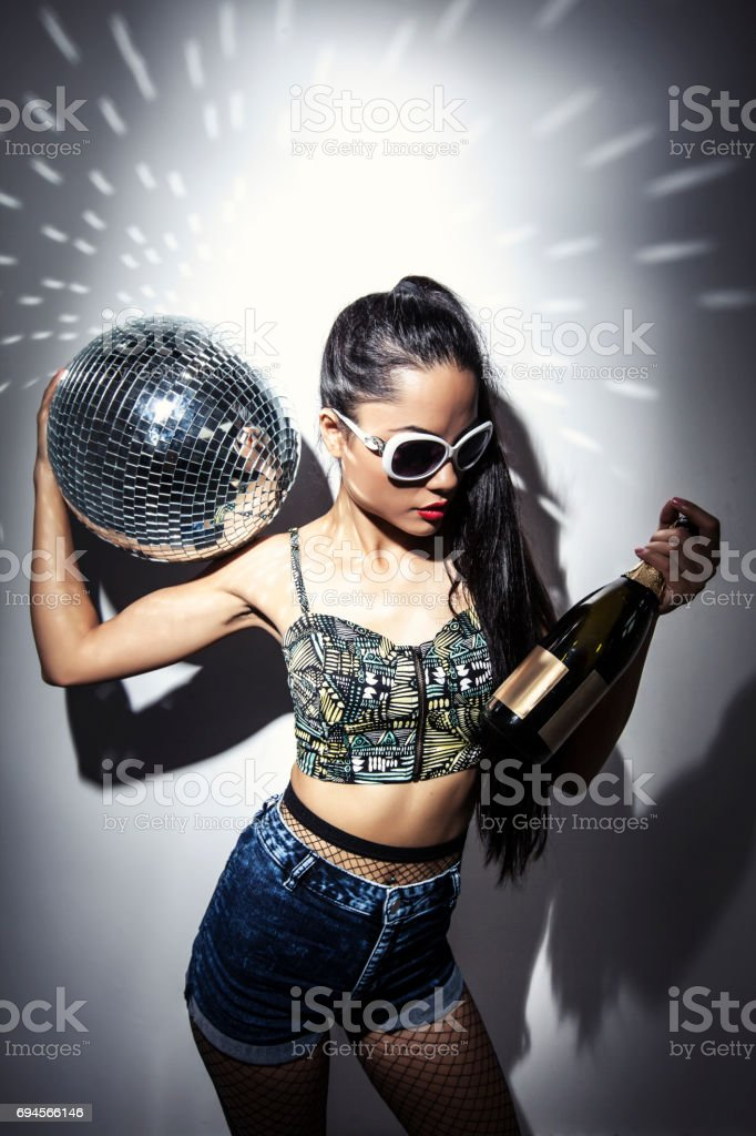 Direct flash portrait of beautiful young woman with disco ball and...