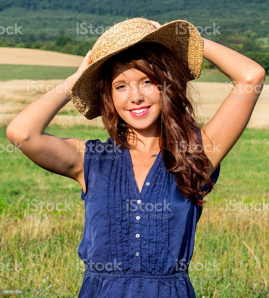 Portrait of beautiful young woman with flowers in the field stock photo