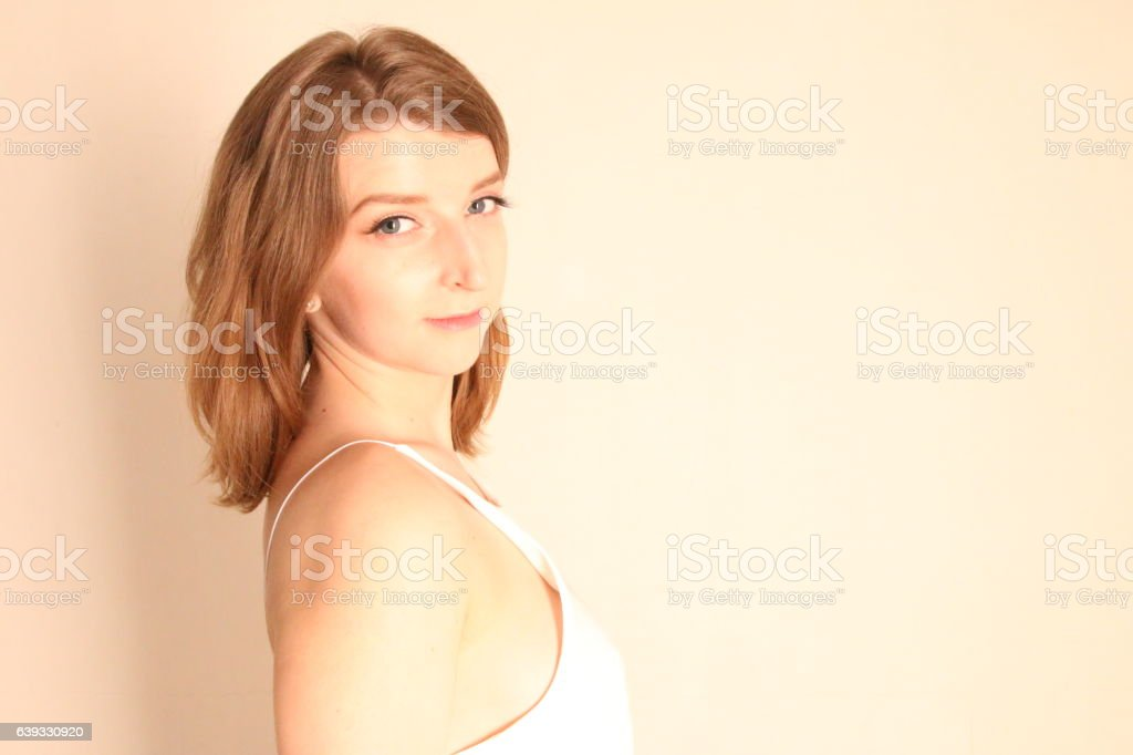 portrait of beautiful young woman with long brown hair posing stock photo