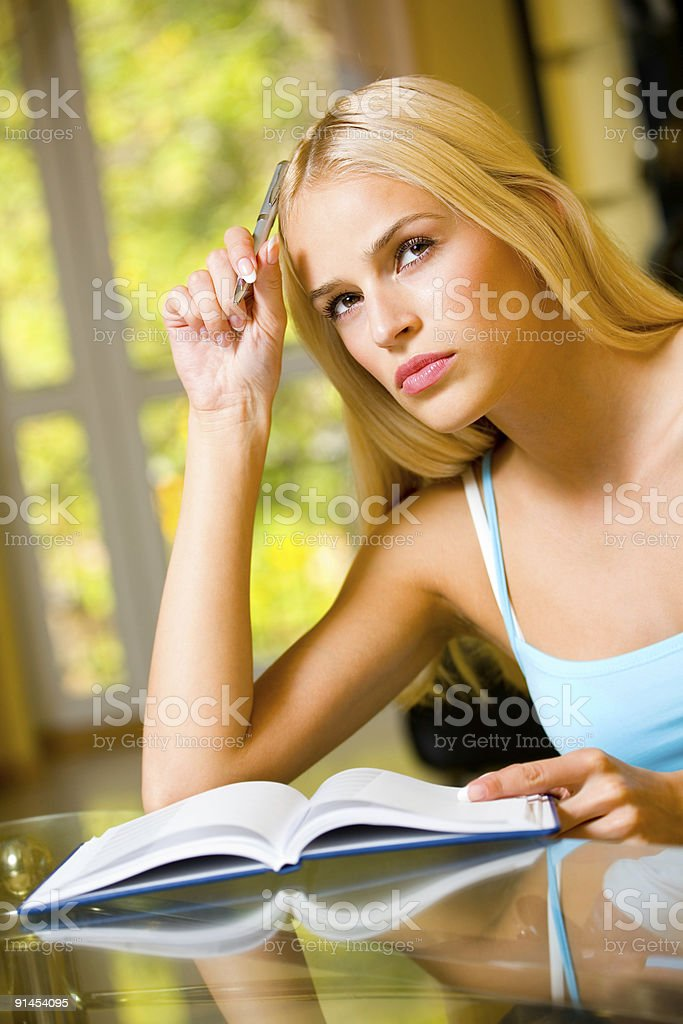 Portrait of beautiful young woman with notebook or organiser, indoors royalty-free stock photo