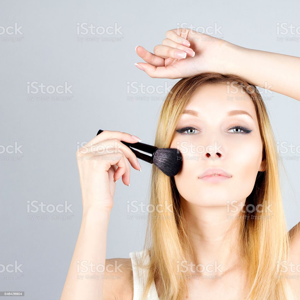Portrait of beauty woman applying foundation with cosmetic brush. Make-up. stock photo