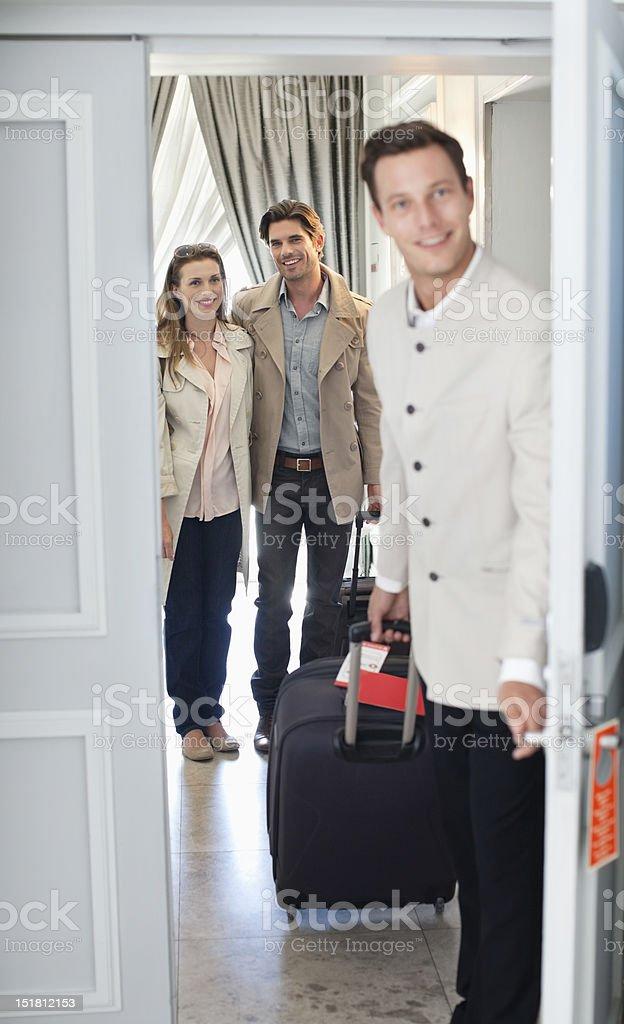 Portrait of bellman opening hotel room door with couple in background stock photo