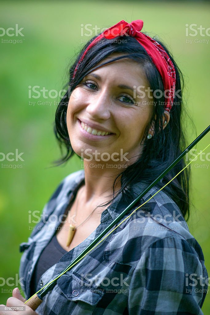 Portrait of Black Haired Woman with a Fly Rod stock photo