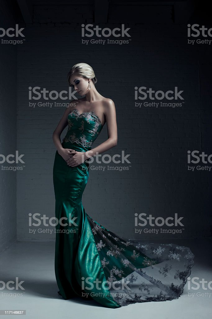 Portrait of blond female model in green evening grown stock photo