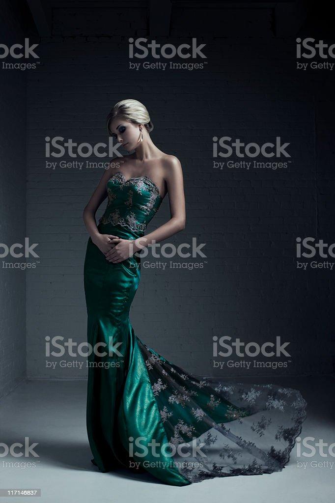Portrait of blond female model in green evening grown stock photo