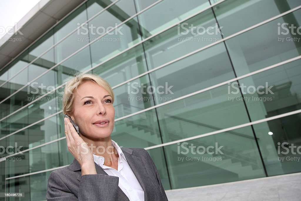 Portrait of blonde mature businesswoman talking on phone royalty-free stock photo