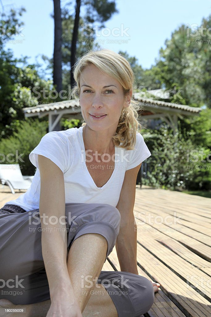 Portrait of blonde mature woman sitting on pool deck royalty-free stock photo