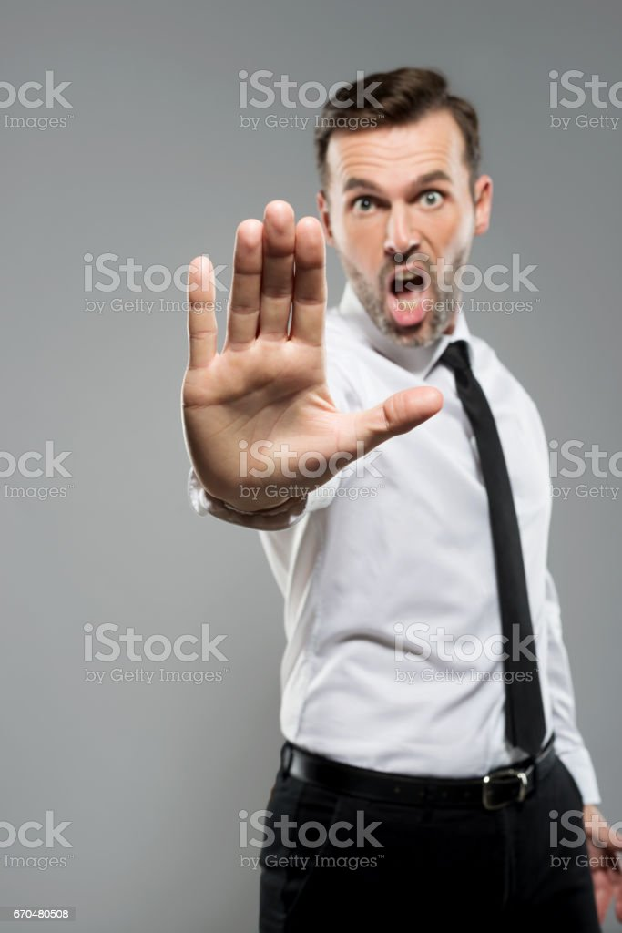 Portrait of bossy businessman gesturing stop, studio shot stock photo