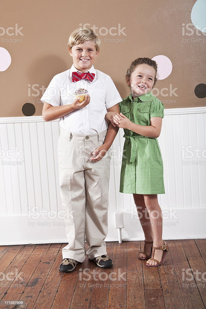 Portrait of boy and little sister, holding cupcake stock photo