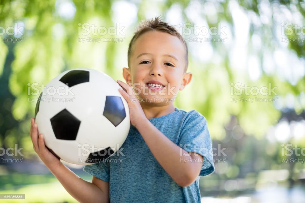Portrait of boy holding a football in park stock photo