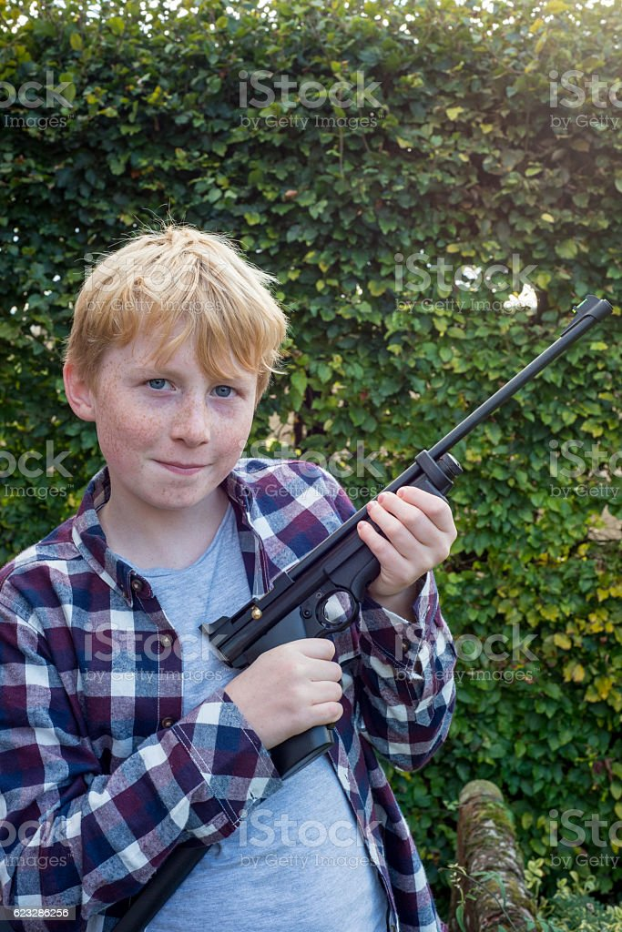 Portrait of Boy Holding an Air Pistol stock photo