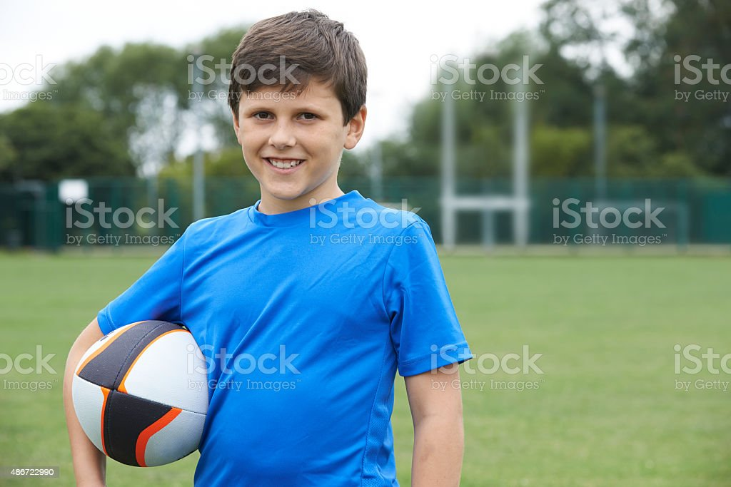 Portrait Of Boy Holding Ball On School Rugby Pitch stock photo