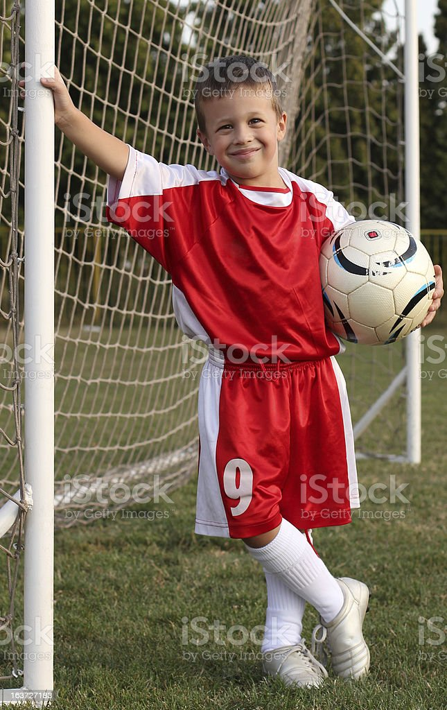 Portrait of boy in soccer kit, holding a football, smiling. royalty-free stock photo