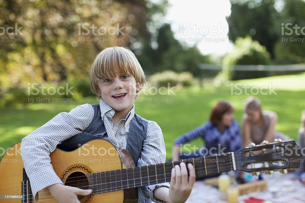 Portrait of boy playing guitar in park stock photo