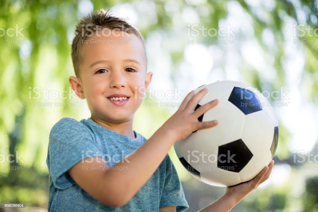 Portrait of boy playing with a football in park stock photo