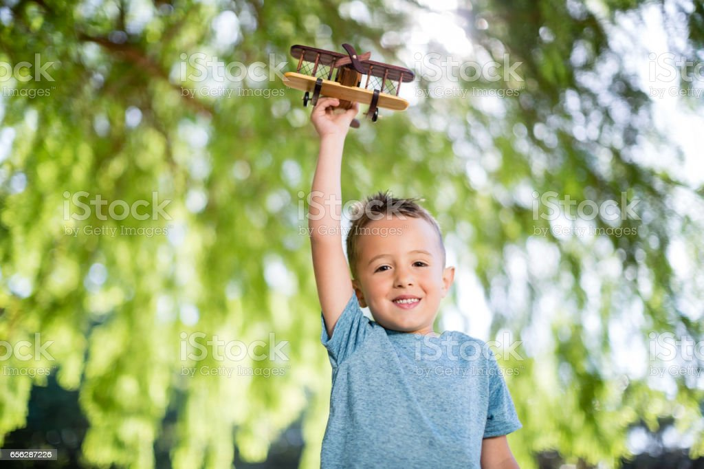 Portrait of boy playing with a toy aeroplane in park stock photo