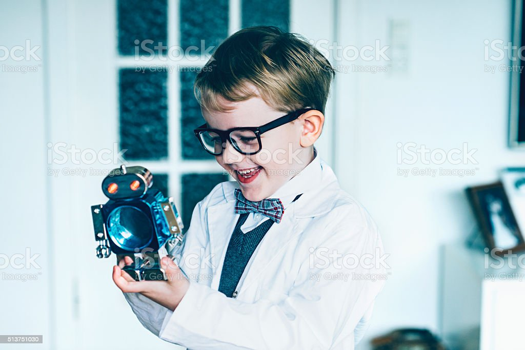 Portrait of boy who plays with toy robot stock photo