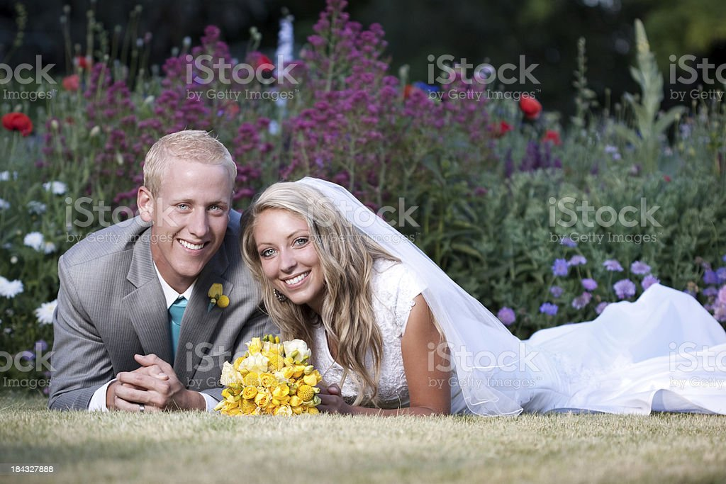 Portrait of Bride and Groom Outdoors with Flower Garden Background royalty-free stock photo