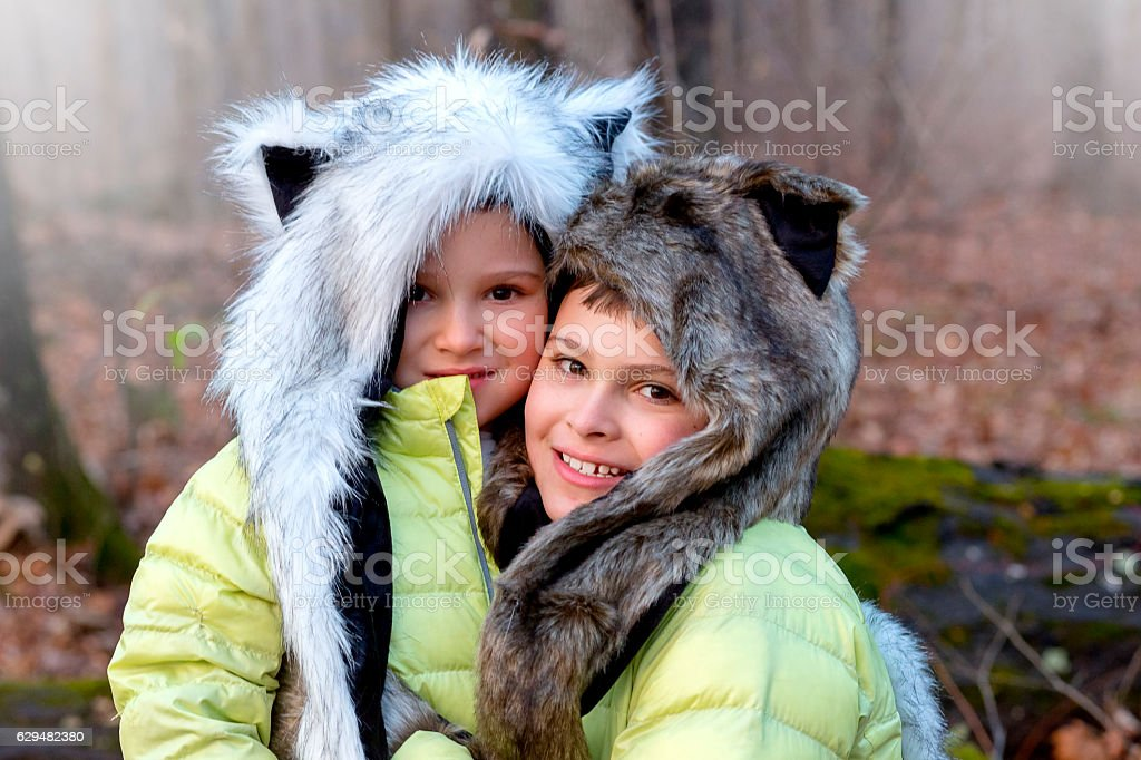 Portrait of brothers wearing animal hats outdoors stock photo
