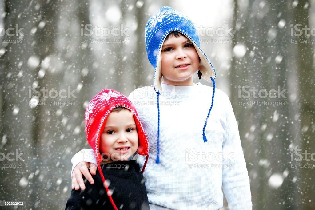 Portrait of brothers with special needs in snowy winter background stock photo