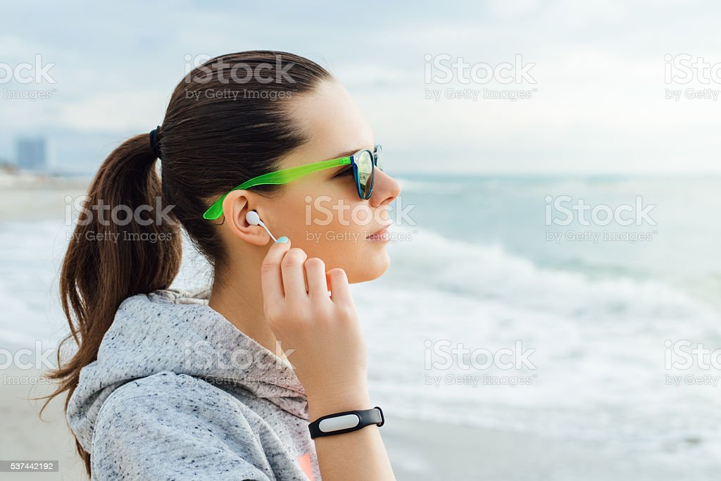 Portrait of brunette in sportswear and sun glasses that listenin stock photo