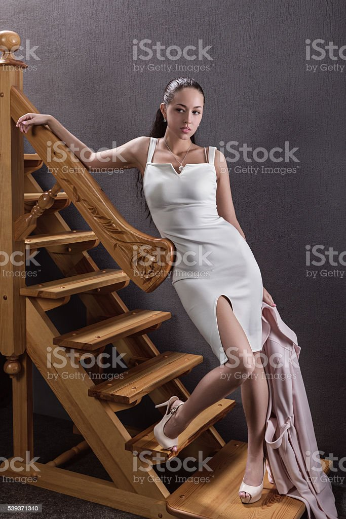 Portrait of brunette in the studio on the stairs. stock photo