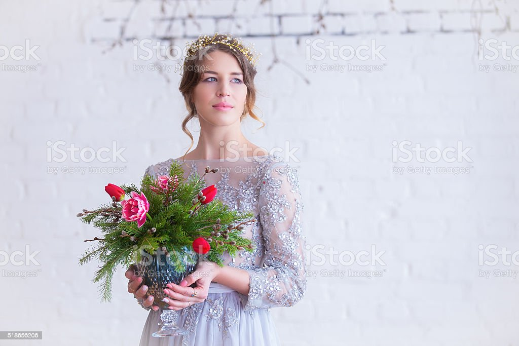 Portrait of brunette in vintage gray dress with bouquet of roses stock photo