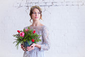 Portrait of brunette in vintage gray dress with bouquet of roses