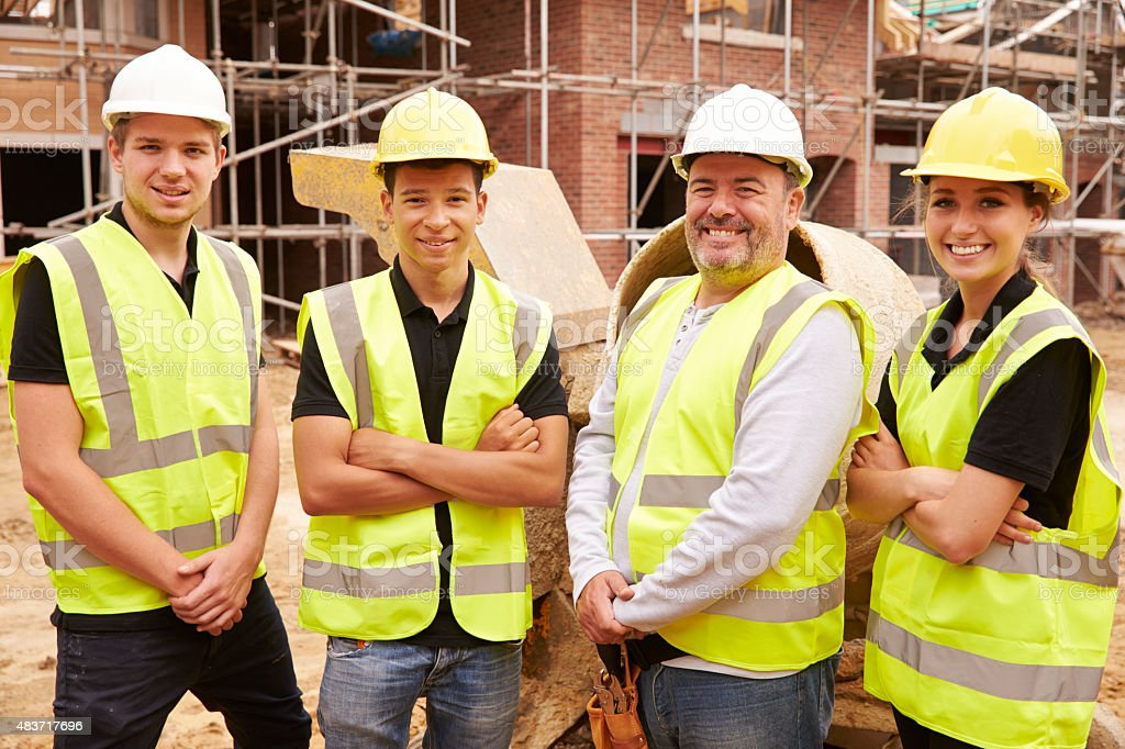 Portrait Of Builder On Building Site With Apprentices stock photo