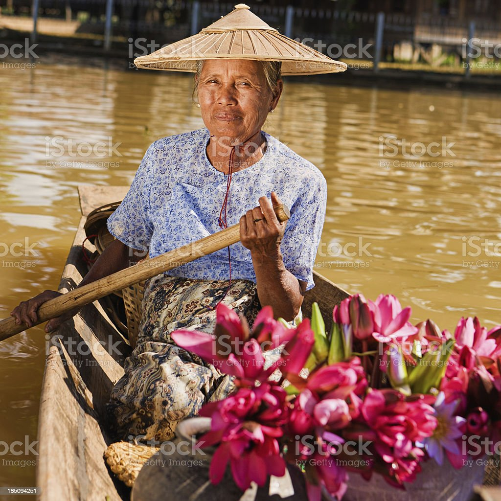 Portrait of burmese woman selling lotus flowers on floating market royalty-free stock photo