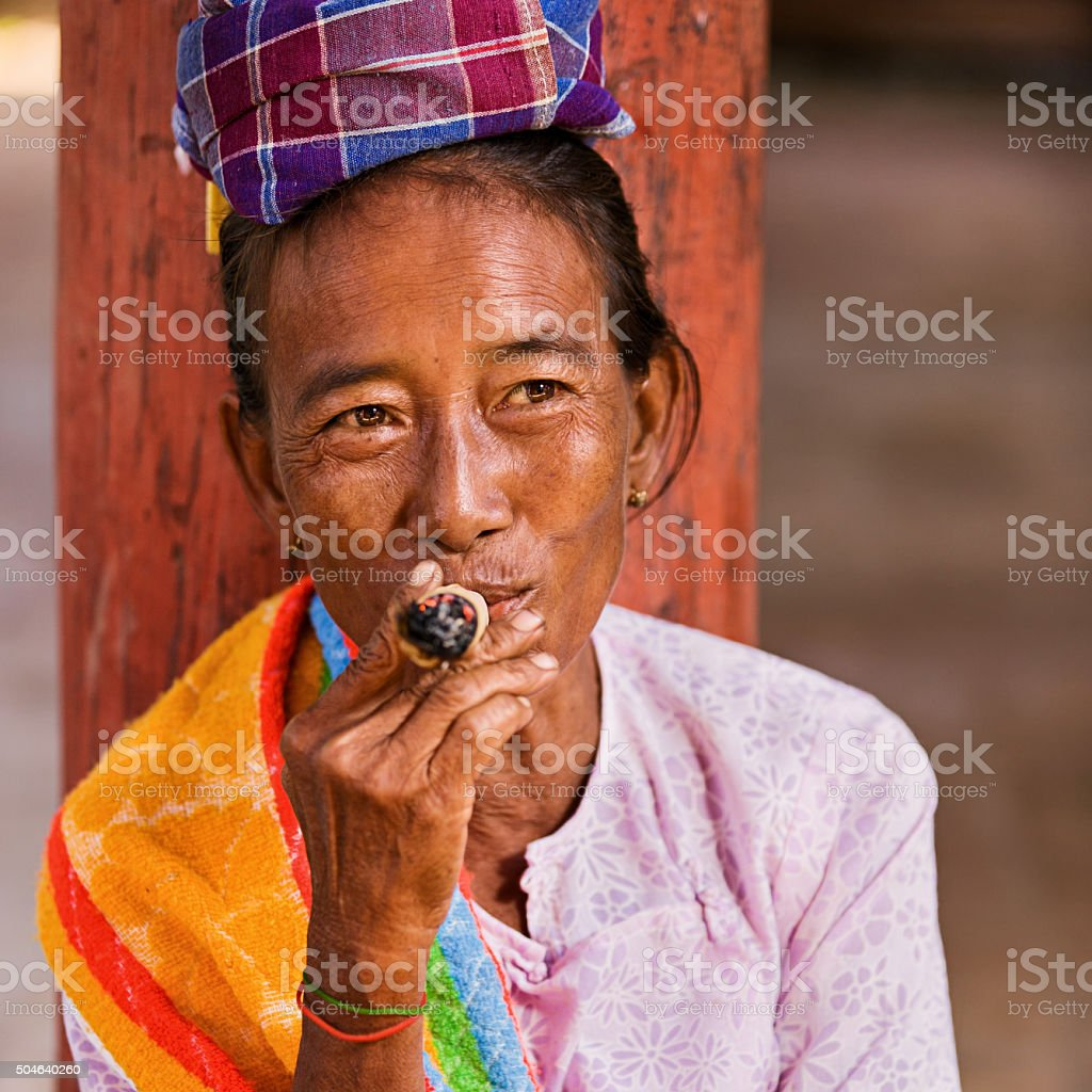 Portrait of burmese woman smoking a cigar stock photo