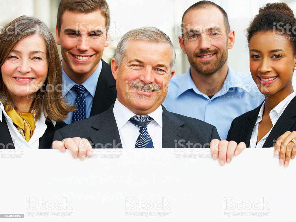 Portrait of business people holding a whiteboard royalty-free stock photo